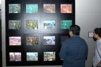 """Kumar (HG) and Lysimachus (HG) looks at  """"The Wall"""", a bank of monitors which allows anyone to see how playtesting is going."""